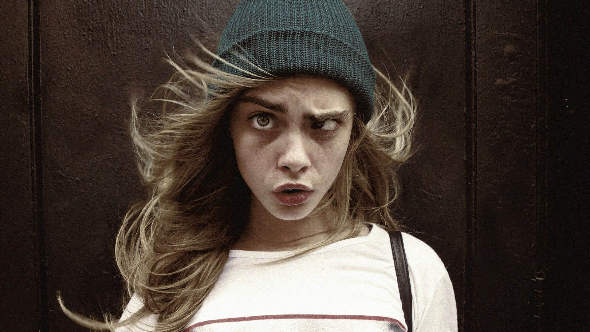 Cara Delevingne in cap squint the eye
