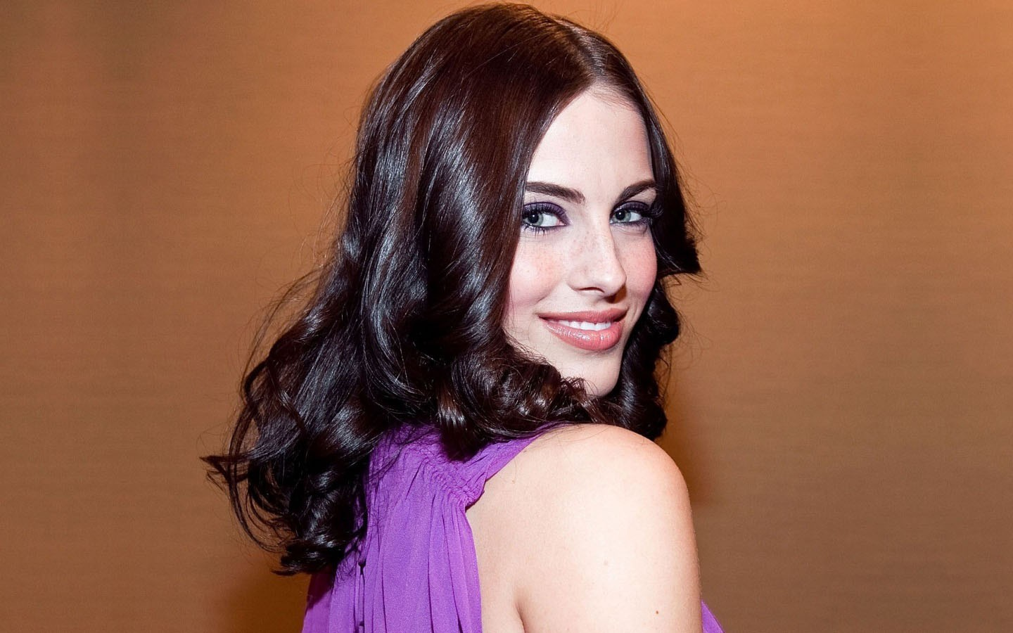 Smiling Jessica Lowndes on the light brown color background