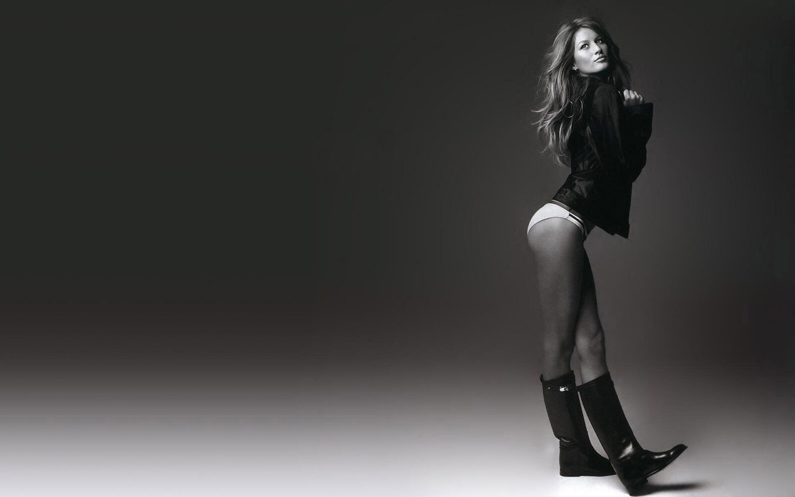 Dark background Gisele Bundchen in black boots