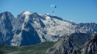 Italy - mountain Marmolada, man with parachute above the mountains