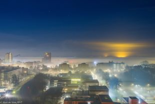 Night city in the fog at sunset