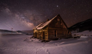 Old house in winter under night sky, Milky Way