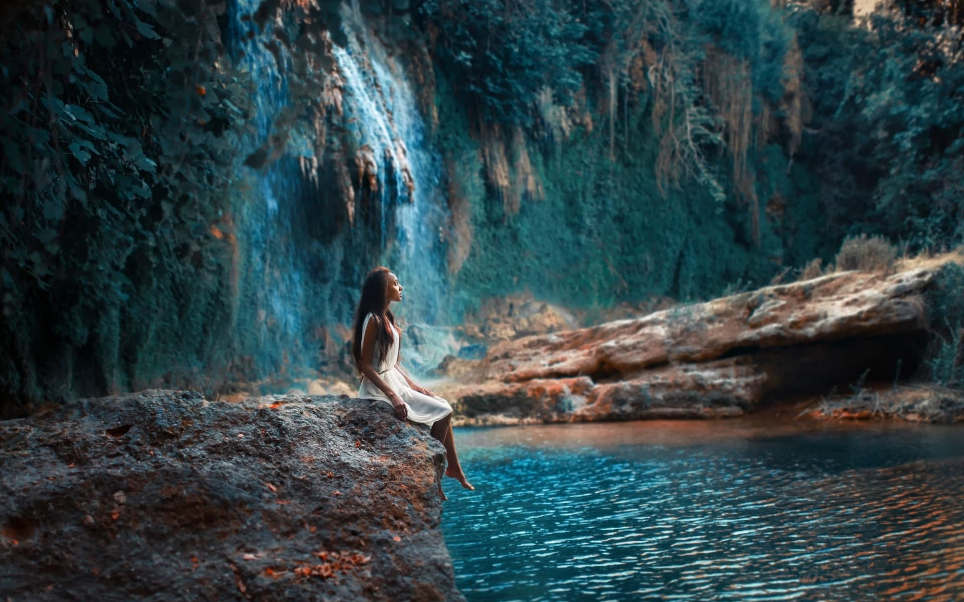 cute girl in white dress on a waterfall background