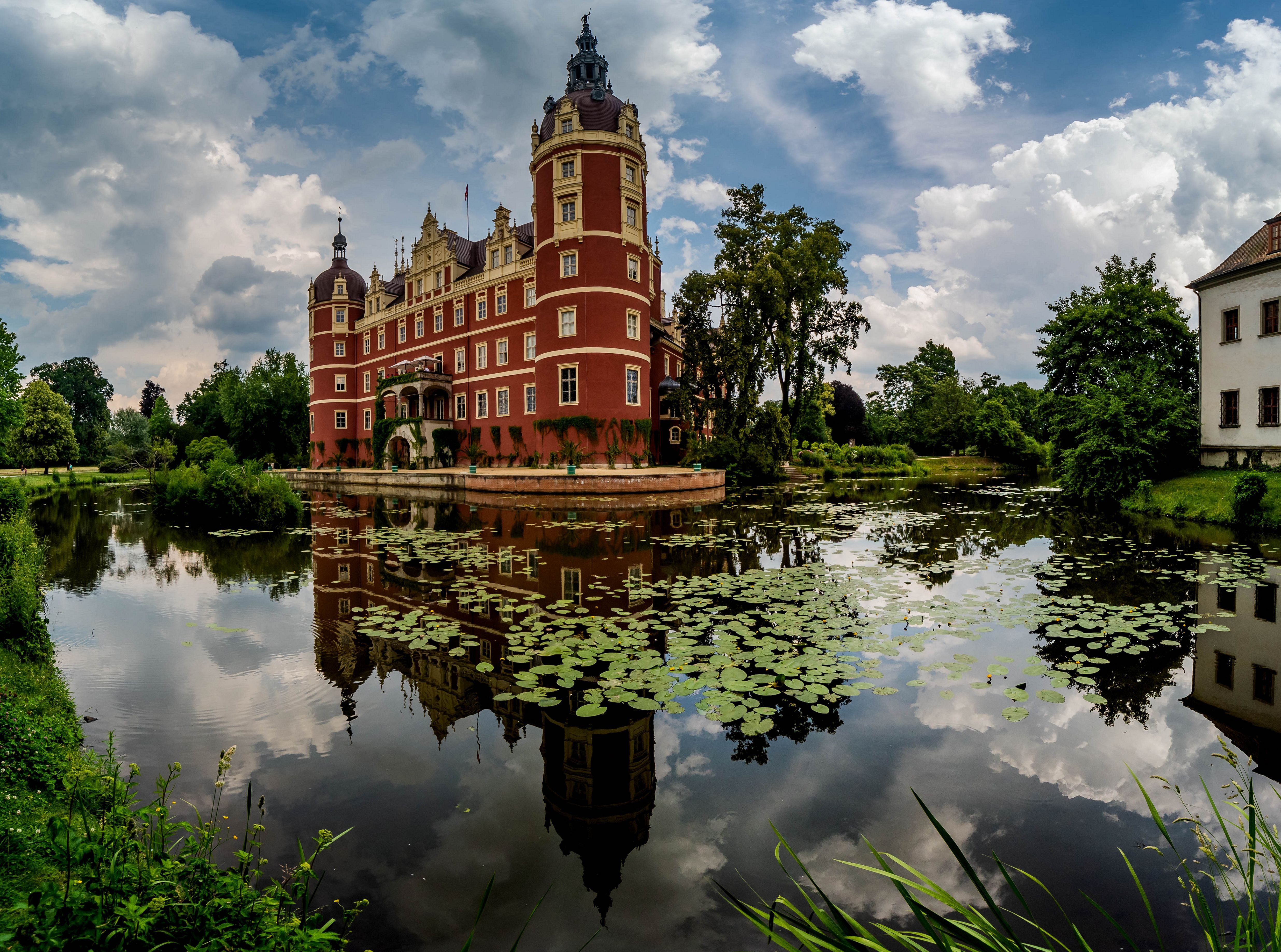 red Castle Muskau on the shore on the lake
