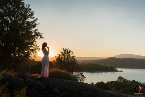 a woman in white dress near a lake at dawn
