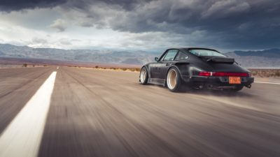 Black widebody sport car on Rotiform MLW wheels - RWB Porsche 911 (993) at speed