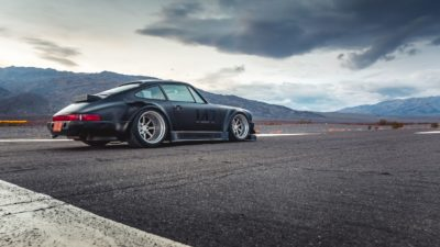 Black widebody sport car on Rotiform MLW wheels - RWB Porsche 911 (993) started in a race