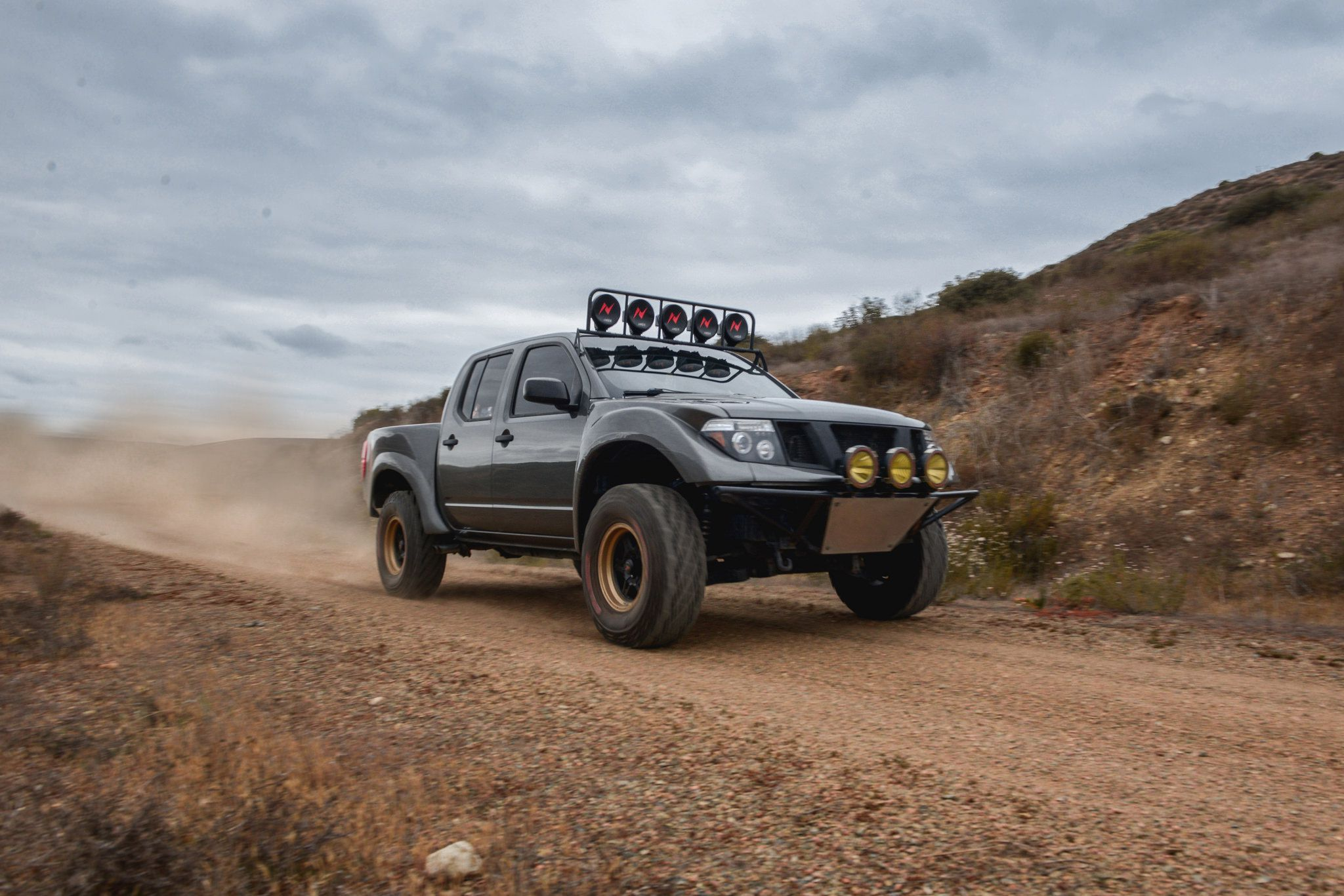 off road suv - dark-grey Nissan Frontier SE with five lights on roof