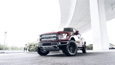 Truck on black Rotiform HUR wheels - 2017 red Ford Raptor F-150 front bumper view