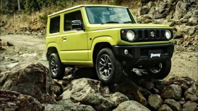 Yellow-green Jimny on rocks