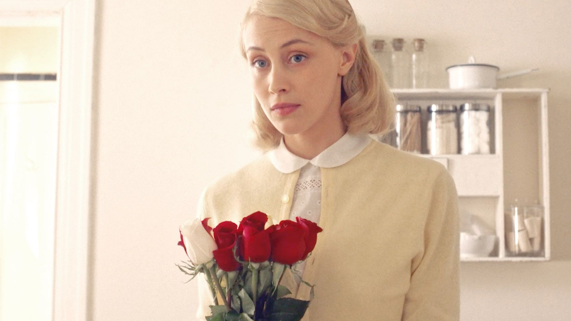 Sarah Gadon as Olivia Hutton with red roses in Indignation
