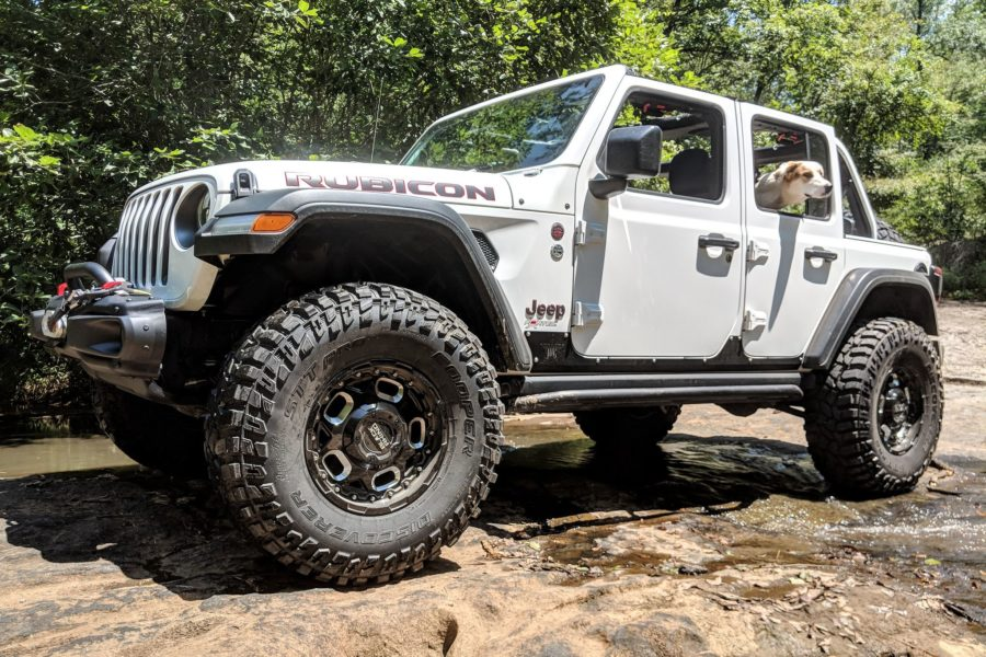 white Wrangler JL Unlimited Rubicon on Rhino Gusset wheels with a dog inside