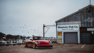red Porsche Cayman on golden Rotiform HUR