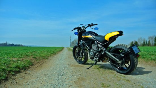 black Ducati Scrambler with yellow stripe