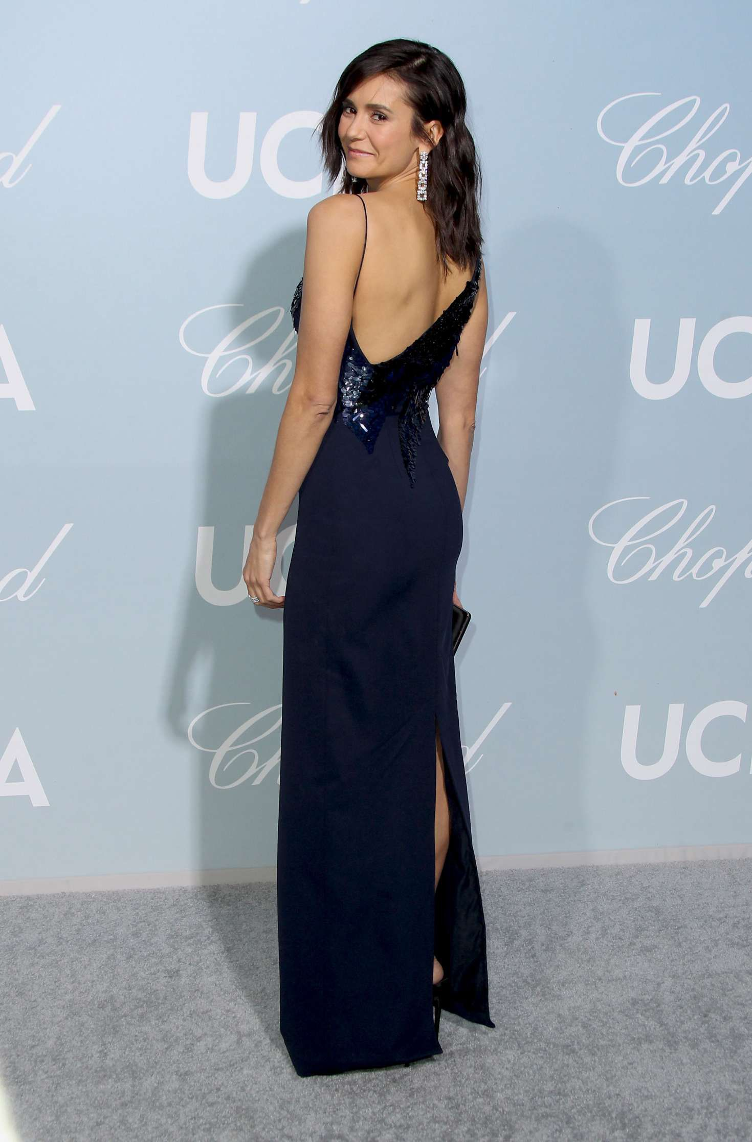 Nina Dobrev in dark blue dress poses for a camera