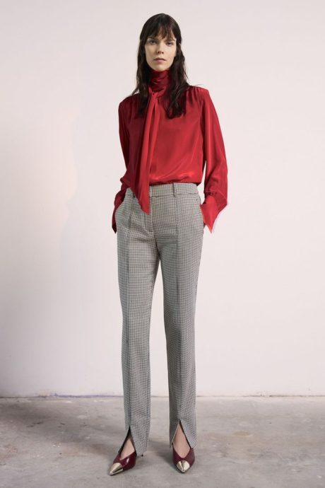 a model in red bluse and long grey pants by Jason Wu