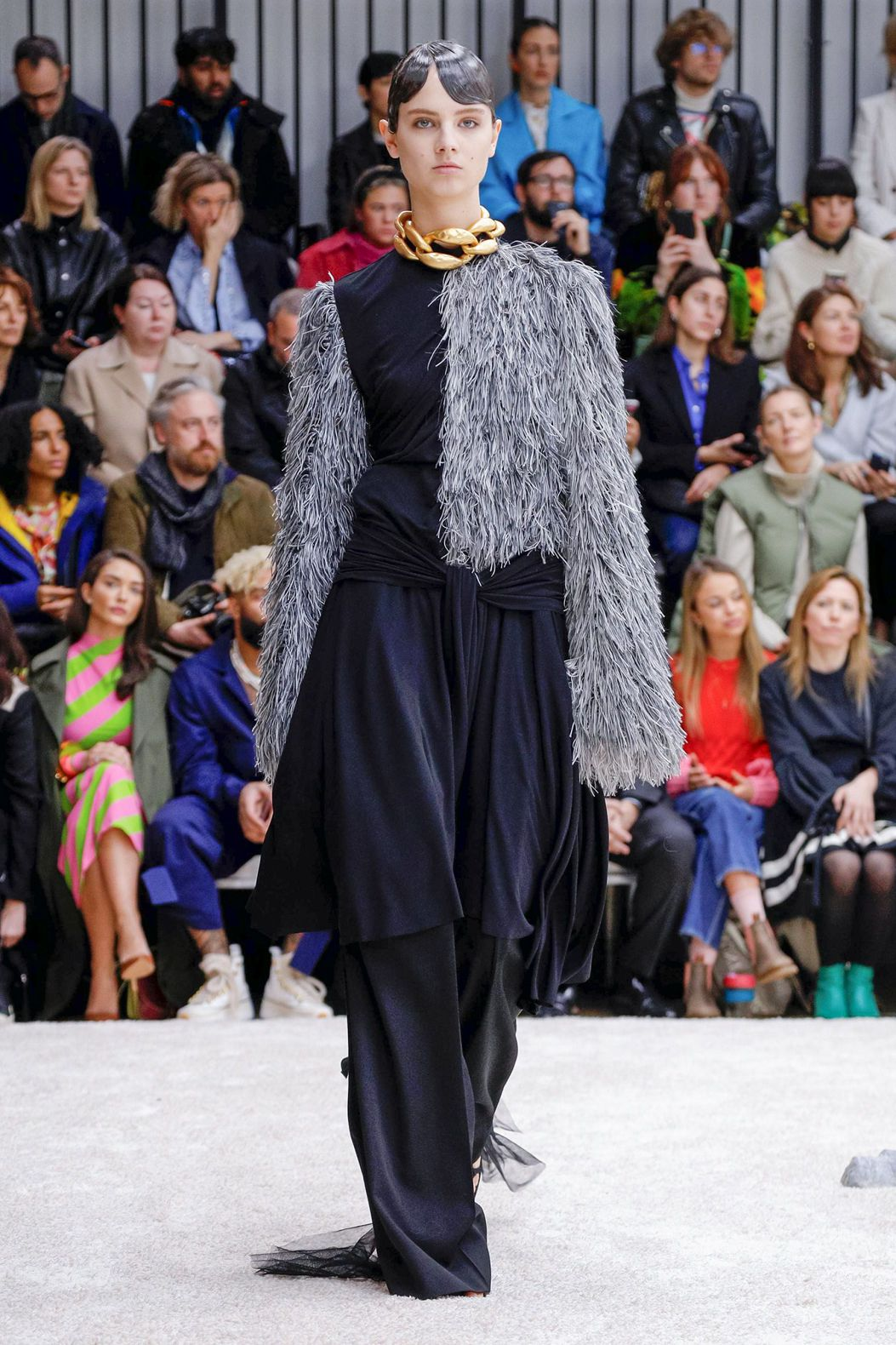 red fluffy jacket on a dark blue long dress by JW Anderson