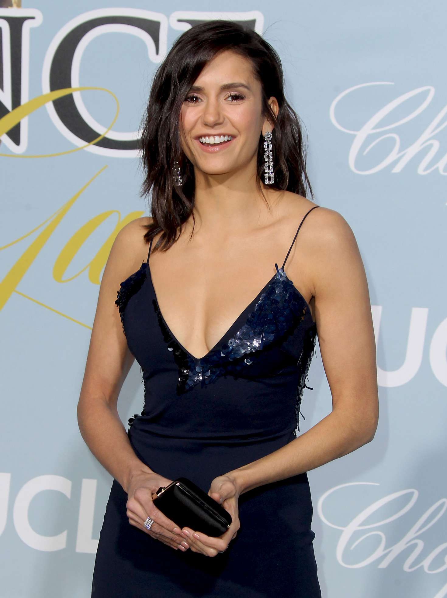 smiles Nina Dobrev in dark blue dress
