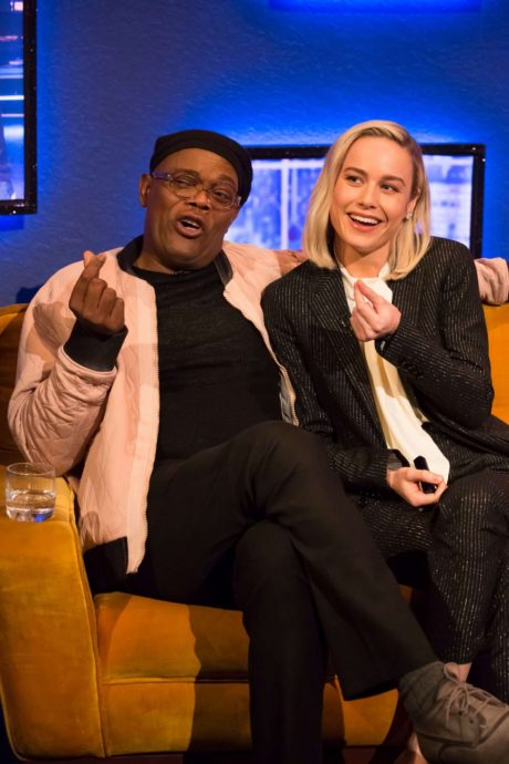 Brie Larson and Jonathan Ross showing modey symbol