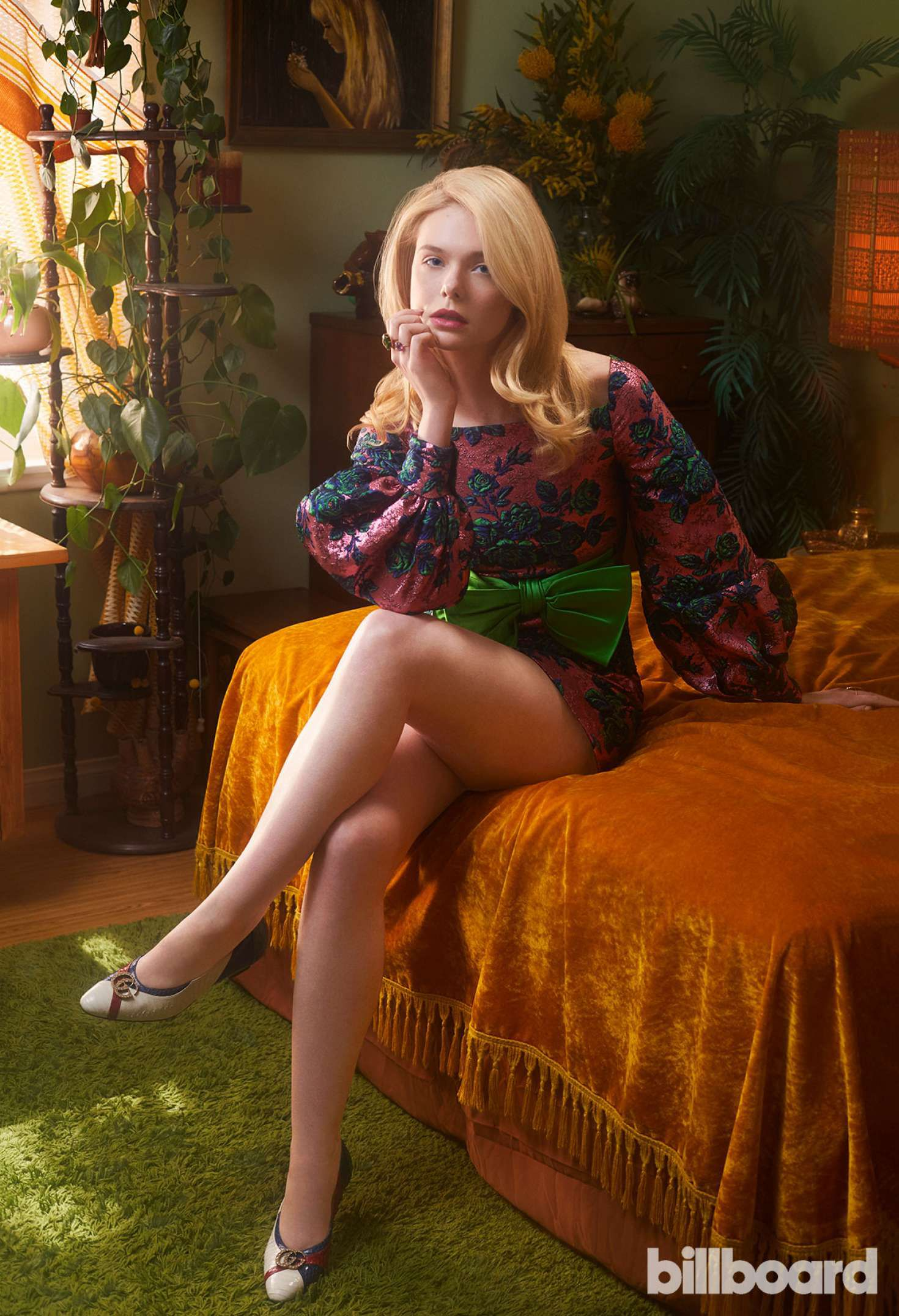 Elle sits on a bed for Billboard Magazine, 2019