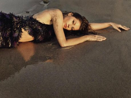 Gisele Bundchen lies on sand in black dress