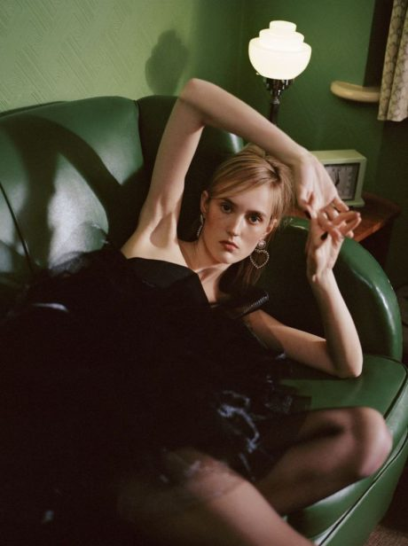 Harleth Kuusik in black dress on a sofa