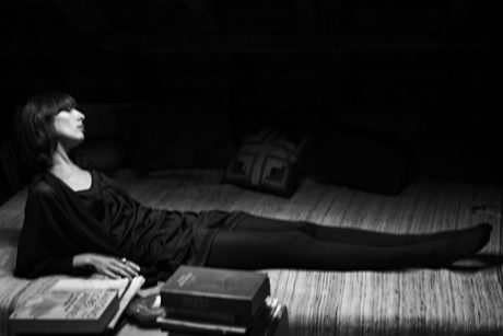 Jamie Bochert lies on a floor in b&w