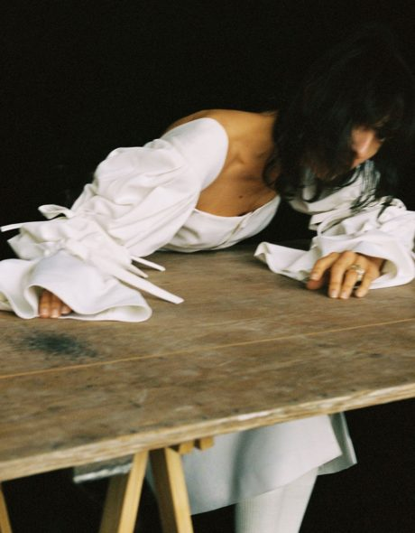 Jamie Bochert lies on a wooden table in white