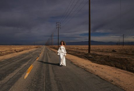 Vanessa Axente alone in white dress on a road