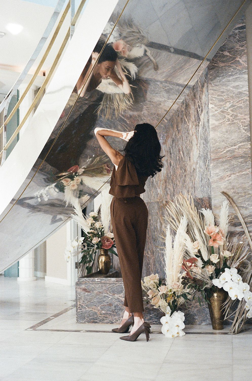 Winnie Harlow in brown suit near a large mirror