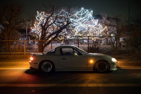 Mazda Miata under lights tree