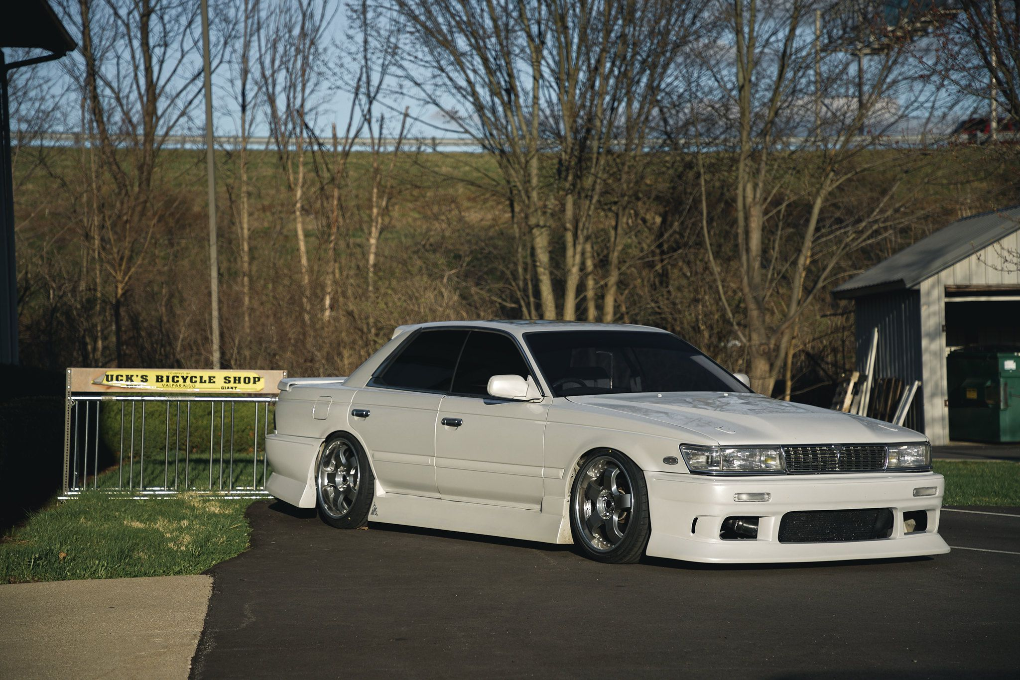 White Nissan Laurel at trees background